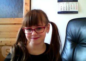 Dívka s červenými brýlemi doma přes Skype