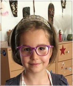 Dívka s fialovými brýleni doma přes Skype